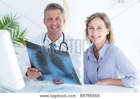 Doctor and patient smiling at camera in medical office