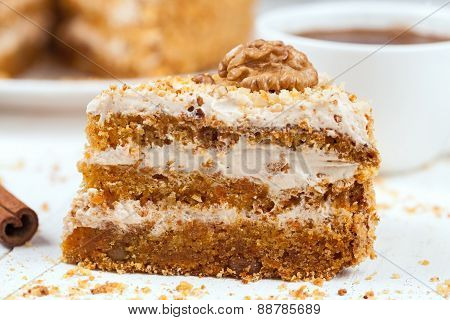 Piece of delicious treat carrot cake sweet dessert with pastry cream, walnut, cinnamon and coffee