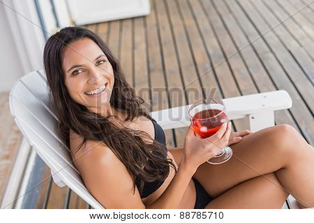 Beautiful woman relaxing and holding drink on sun lounge