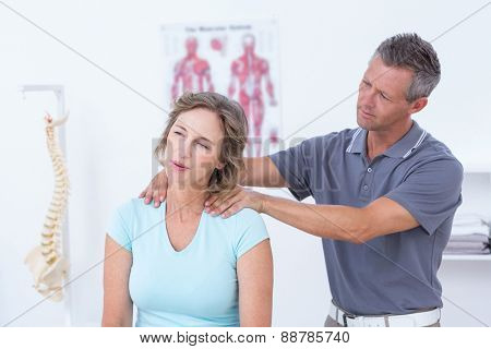 Doctor massaging his patient shoulders in medical office