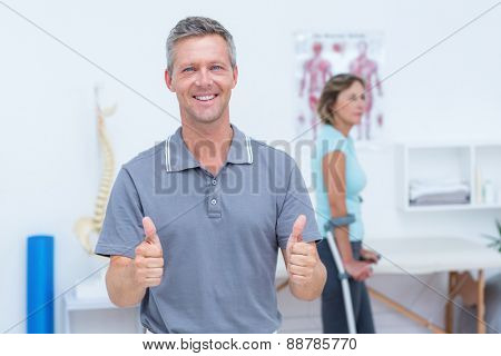 Doctor smiling at camera while his patient standing with crutch in medical office