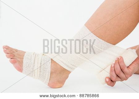 Sitting woman banding her ankle on white background