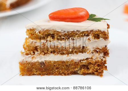 Slice of gourmet easter cake with cream and little orange carrot