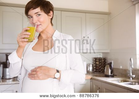Pregnant woman drinking glass of orange juice at home in the kitchen
