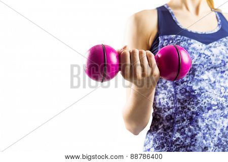 Fit woman lifting pink dumbbell on white background