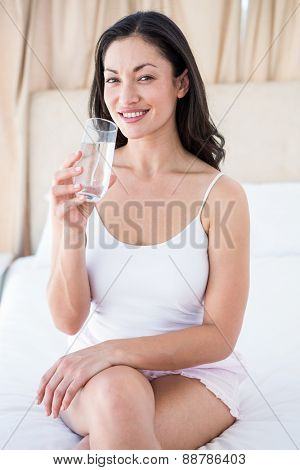 Pretty brunette holding a glass of water on bed at home