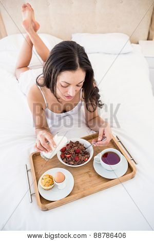 Pretty brunette eating her breakfast on bed at home