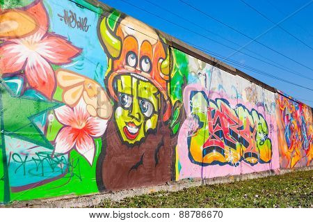 Colorful Graffiti With Cartoon Character Over Old Gray Concrete Garage Wall