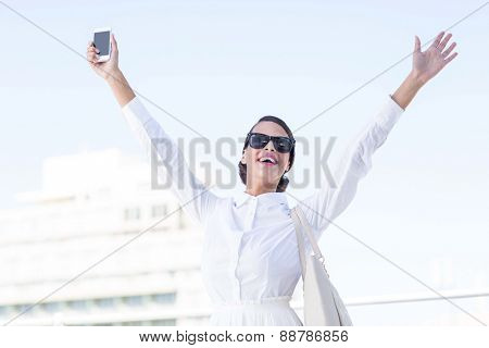 Euphoric woman holding smartphone with hands up outside