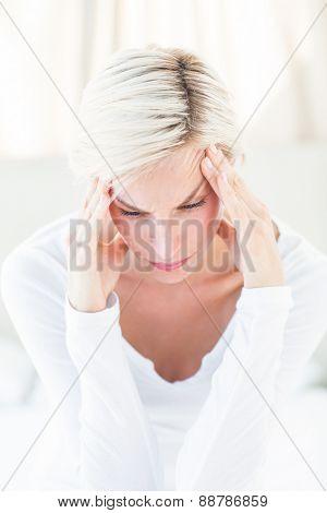 Blonde woman having headache in the bedroom