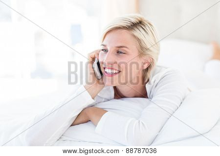 Smiling blonde woman lying on the bed and calling on the phone in her bedroom