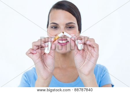 Happy woman breaking a cigarette on white background
