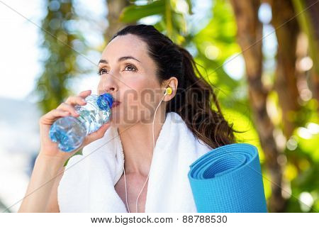 Fit beautiful brunette drinking water while listening music on a sunny day