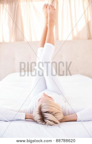 Smiling blonde woman lying on the bed in her bedroom