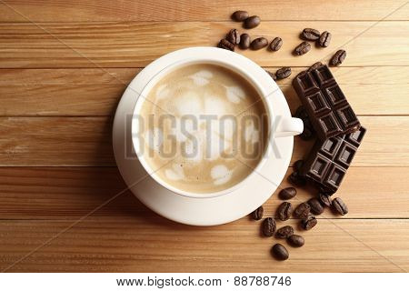 Cup of coffee latte art with grains and chocolate bar on wooden table, top view