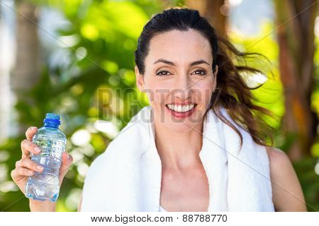 Beautiful brunette holding bottle of water on a sunny day