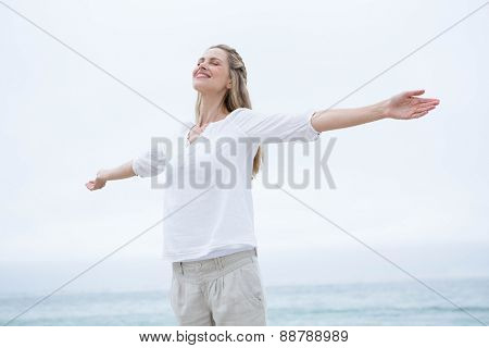 Smiling pretty blonde standing by the sea arms outstretched at the beach