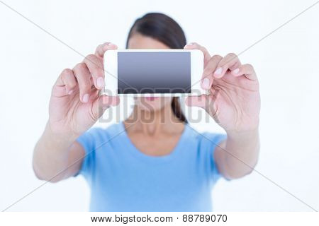 Brunette woman taking a selfie with her smartphone on white background