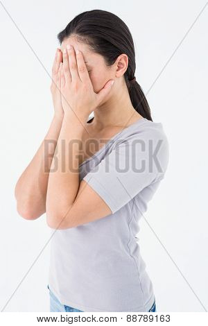 Sad brunette hiding her face on white background
