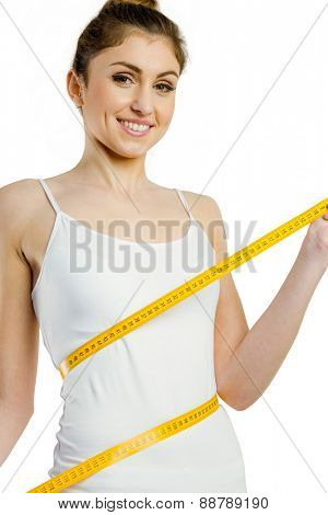 Slim woman measuring her waist on white background
