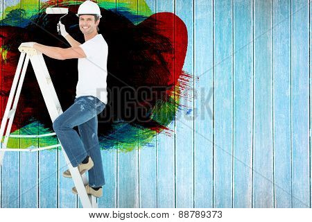 Portrait of man on ladder painting with roller against wooden planks