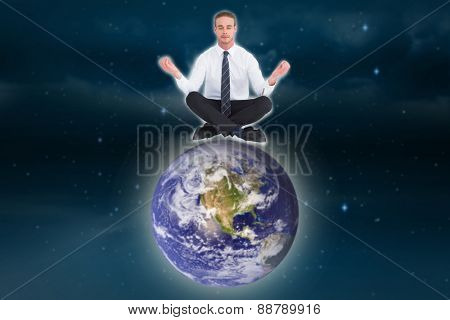 Businessman meditating in lotus pose against stars twinkling in night sky