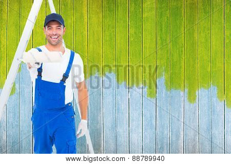 Handyman using paint roller on white background against wooden planks