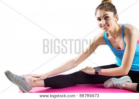 Fit woman stretching on exercise mat on white background