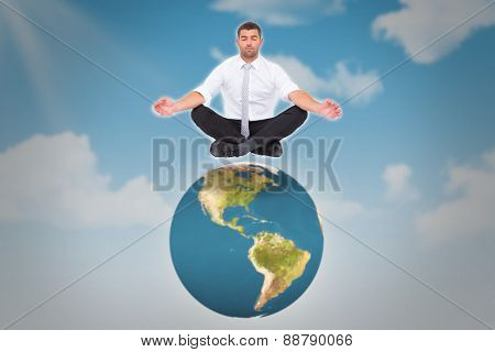 Businessman meditating in lotus pose against blue sky