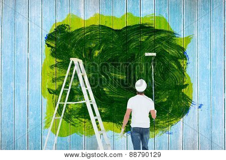 Man with paint roller standing by ladder against wooden planks