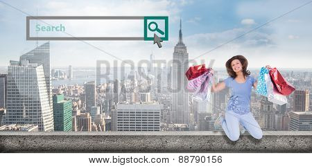 Excited brunette jumping while holding shopping bags against large city