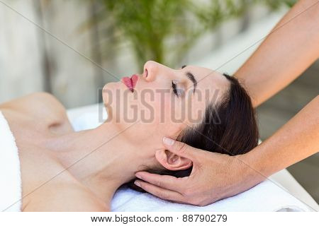 Brunette receiving head massage at the spa