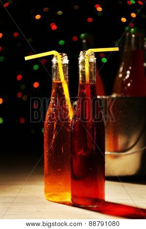 Alcoholic cocktails in glass bottles with straws on dark bright background