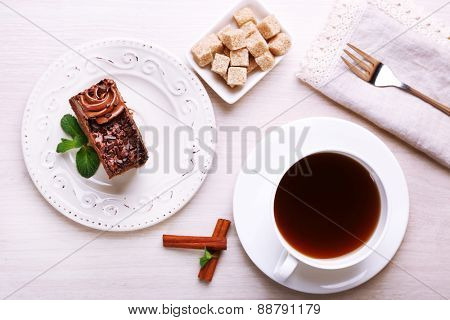 Tasty piece of chocolate cake with mint and cinnamon near cup of tea and lump sugar on wooden table background