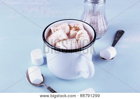 Mug of cocoa with marshmallows on wooden table background