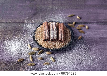 Spices with sugar on color wooden table background