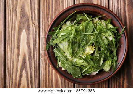 Lettuce with arugula in bowl on wooden background