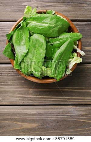 Mix of salad leaves in bowl on wooden planks background