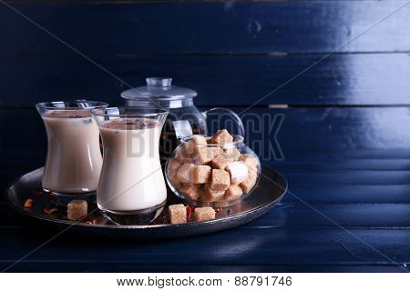 Black tea with milk in glasses and teapot with lump sugar on metal tray and color wooden planks background