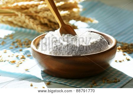 Bowl of flour with spoon and napkin on wooden table, closeup