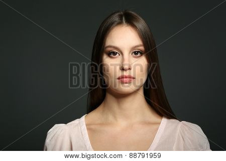Portrait of beautiful young woman on dark background
