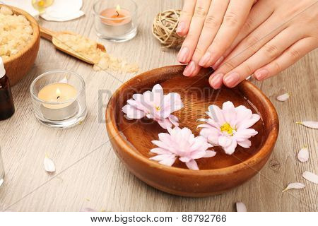 Female hands and bowl of spa water with flowers, closeup