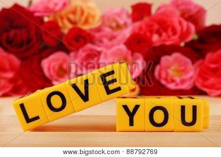 Words Love You formed from cubes with flowers on bright background