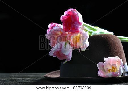 Bouquet of tulips and hat on black background