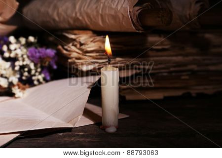 Still life with retro books and candlelight on wooden table, closeup