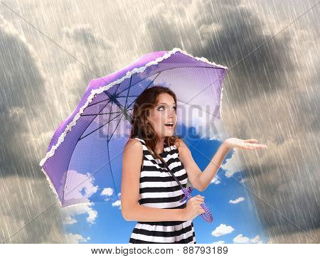 Girl with umbrella standing under the rain