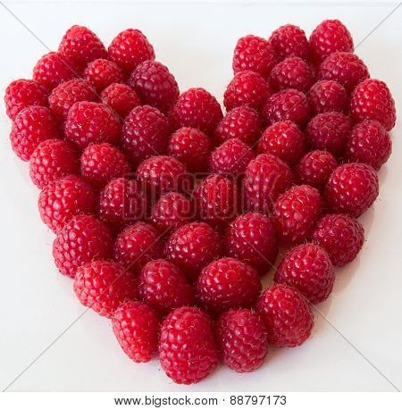 Close up of red raspberries in the shape of a heart