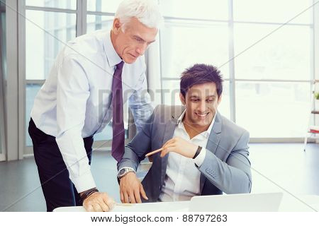 Two businessman in office having discussion in front of computer