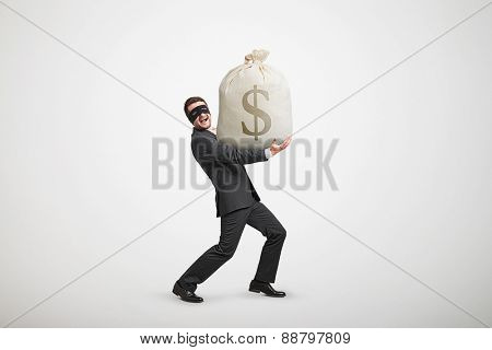laughing man in formal wear and black mask on the eyes holding big bag with money and looking at camera against light grey background