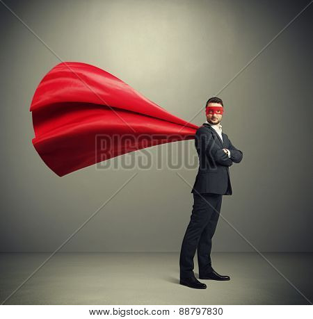 serious businessman dressed as a superhero in red mask and cloak over dark grey background